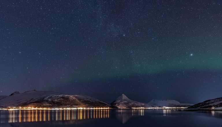 Der Sternenhimmel über einem Fjord in Senja