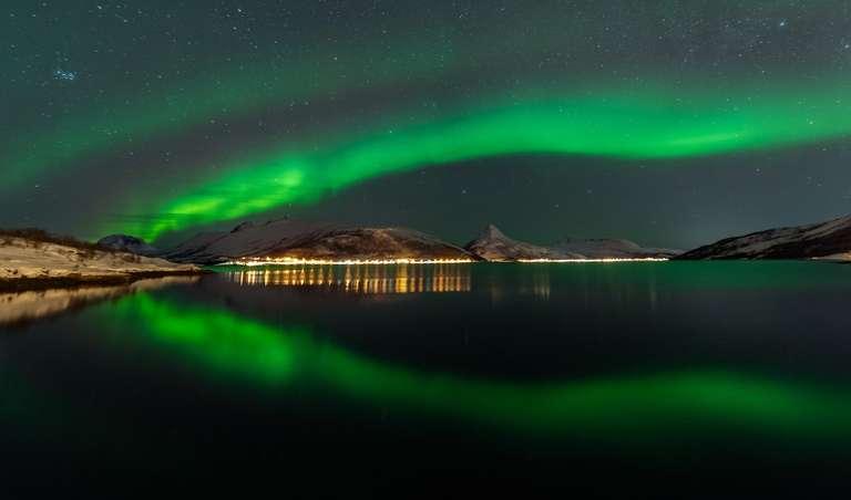 Spiegelung von Nordlichter über einem Fjord in Senja