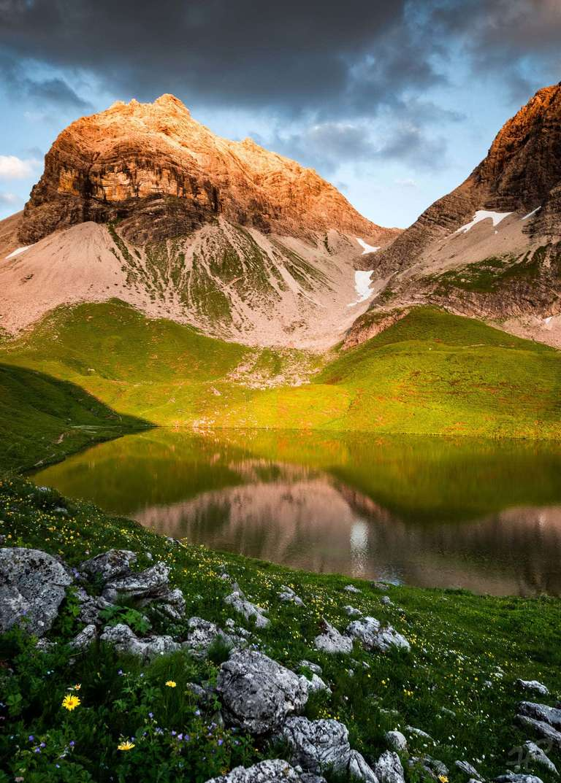 Alpenglühen an einem Bergsee im Allgäu