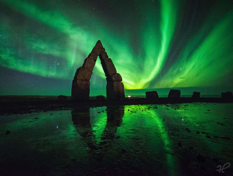 Felsformation mit Polarlicht auf Island