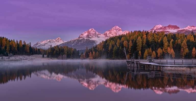 Sonnenaufgang mit Alpenglühen an einem See im Engadin