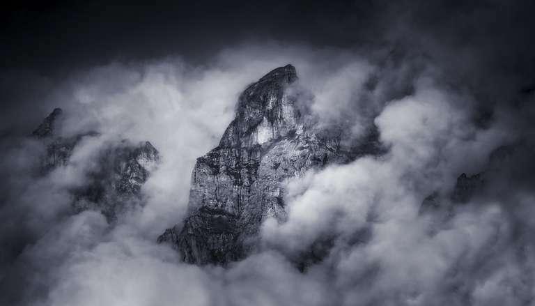 Giant In The Sky - Ein Foto von Fotograf Nick Schmid. Es zeigt ein mystisches schwarz-weiß Motiv aus den Schweizer Alpen. Dieses kunstvolle Foto ist besonders als Fine Art Druck auf Hahnemühle Papier geeignet. Aber auch als Wandbild auf einem anderen Material ist es sehr sehenswert.