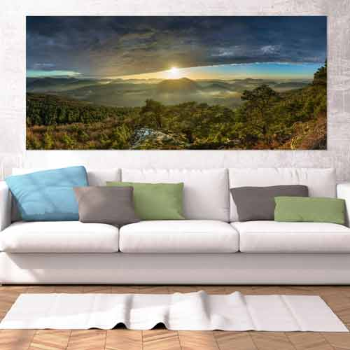 Ein Fine Art Panorama Wandbild von Heimatfotos, gedruckt im UV-Direktdruck hinter mattes Acrylglas, in einem Wohnzimmer über dem Sofa. Das Wandbild zeigt ein Panorama aus dem Pfälzer Wald bei Sonnenuntergang mit Wolken. Das Foto ist von unserem Heimatlicht und Fotograf Christian Fernandez Gamio