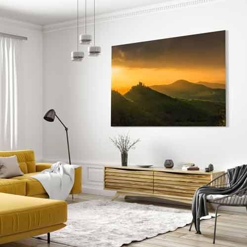 Ein im UV-Direktdruck auf Holz gedrucktes Wandbild von Heimatfotos in einem modernen Wohnzimmer . Das Wandbild zeigt die Reichsburg Trifels in der Pfalz (Pfälzerwald) in einem ganz besonderen Licht. Das Foto ist von unserem Heimatlicht und Fotograf Niko Benas aus Karlsruhe