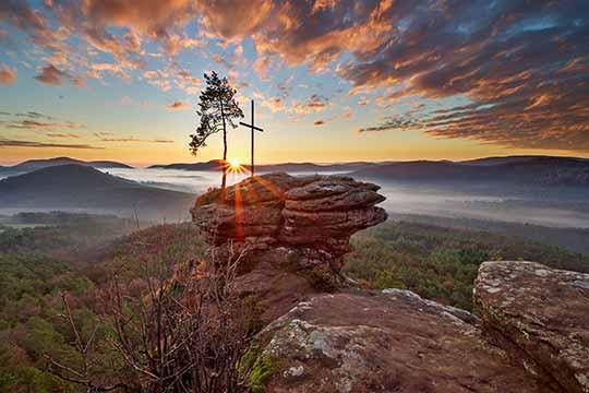 Morgenstimmung auf dem Rötzensteinpfeiler - Ein typisches Motiv aus dem Pfälzerwald (Pfalz), von Fotograf Rüdiger Hauser aufgenommen. Es zeigt einen Felsen im Pfälzerwald mit einem Gipfelkreuz. Unterhalb nebelverhangene Täler. Das Foto ist als hochwertiges Wandbild auf Leinwand, Alu-Dibond, Fotopapier, Leuchtkasten, Holz und hinter Acrylglas (Plexiglas) verfügbar